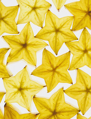 Slices of organic starfruit on white background
