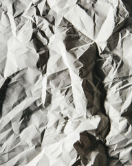 A piece of recycled white paper, crumpled and scrunched up, refuse.