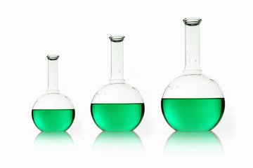 Three rounded shaped scientific chemical flasks holding green liquid, arranged in size order.