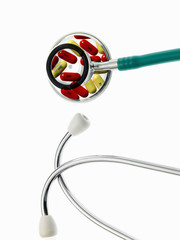 The two parts of a doctor's stethoscope with green tubing, a conceptual illustration of alternative medicine and wellbeing. Medication, pills in the chest piece. Ear pieces.