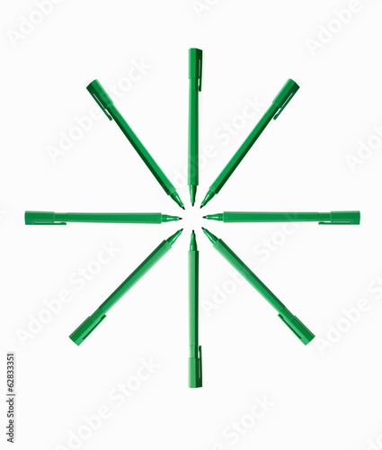Office supplies. Green coloured pens, felt nibs and pen top cases, arranged in a star shape.