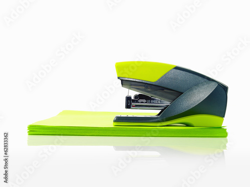 A blue and green plastic stapler, and green post it notes.