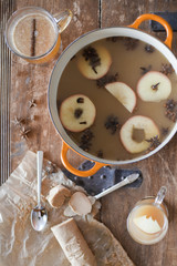 Overhead view of a kitchen table. A large cooking pan with double handles. Sliced cored apples, cloves and star anise with cinnamon. Making a mulled fruit drink.