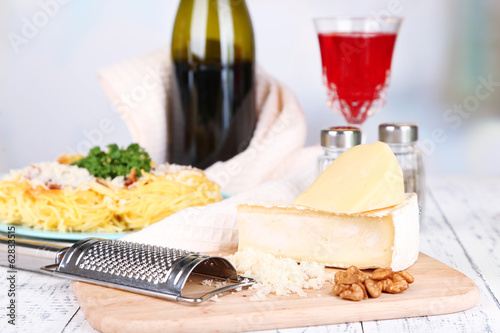 Composition with tasty spaghetti, cheese, wine bottle and glass