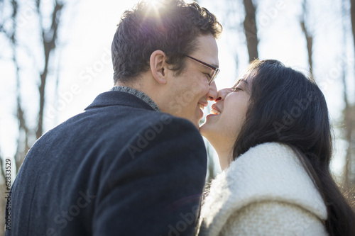 Two people, a couple, a man and woman in the woods on a winter day. Kissing.