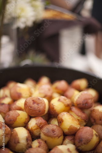 A wedding buffet meal. A dish of partly peeled new potatoes.