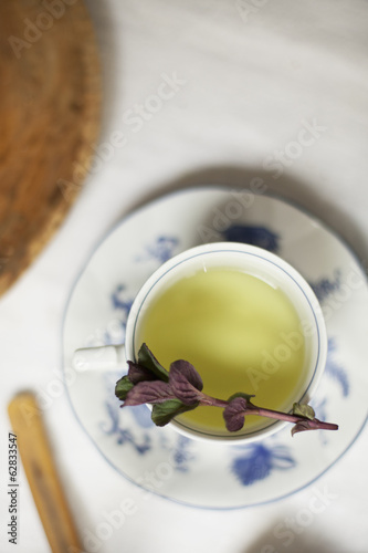A cup of tea, clear coloured tea in a china cup, with a sprig of aromatic mint.