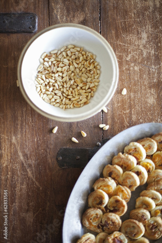 A white pottery bowl, full of dried corn kernels. A dish of baked pastries.