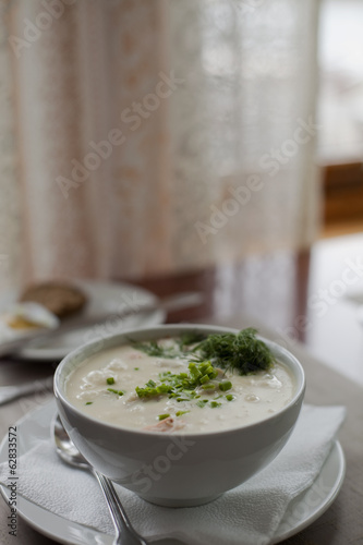 A table setting. A white china bowl of soup, with garnish. A table napkin. Wedding Table Decoration.