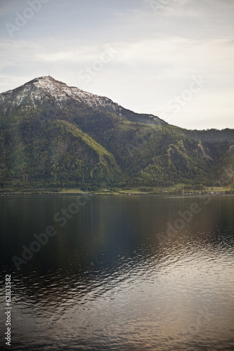 A mountain peak towering over a lake, creating a reflection on the calm water surface.