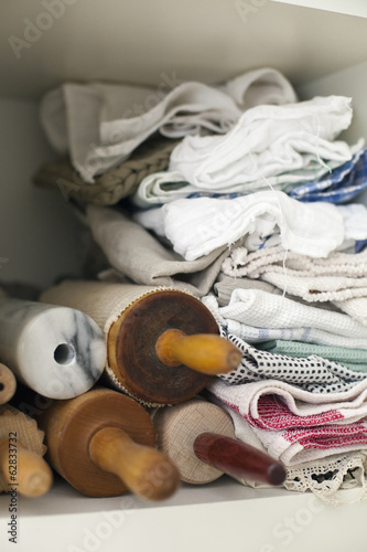 A shelf piled high with cloths, linen and a small stack of rolling pins or wooden spindles.