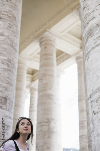 A woman looking up at the tall pillars and arches of a historic building in Rome.