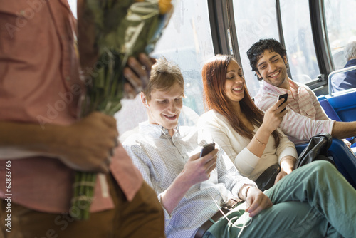 Urban Lifestyle. A group of people, men and women on a city bus, in New York city. Two people checking their phones. One man standing holding a bunch of flowers.
