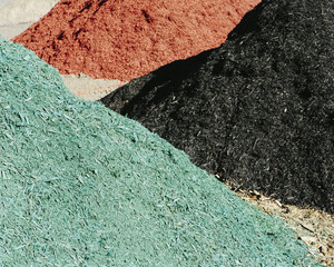 Piles of multi-colored bark wood chips used for landscaping, near Quincy