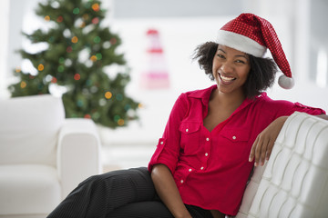 A woman wearing a red and white Father Christmas hat. Sitting on a sofa. Decorated tree.