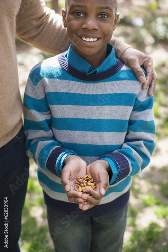 A New York city park in the spring. Sunshine and cherry blossom. A mother and son, a boy holding a handful of nuts.