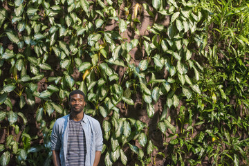 A man standing in front of a wall covered in climbing plants and ivy.