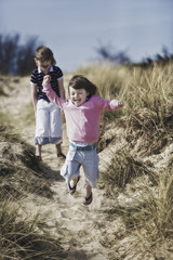 Two young children playing in the dunes.