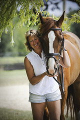A woman standing next to a bay horse with a halter rein.