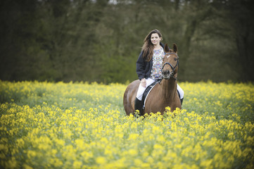 A woman riding on a brown horse through a flowering yellow mustard crop in a field..