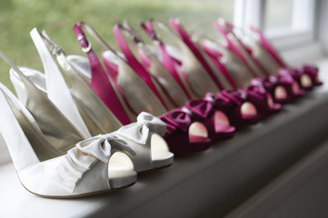 A row of high heeled shoes. Pairs of peep toe slingbacks in white and pink.  Special occasion.