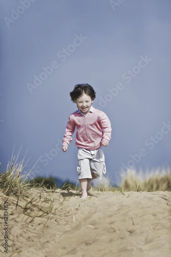 A young boy with brown hair running on a beach.