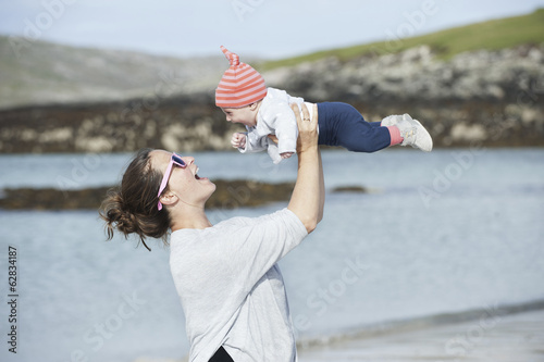 A mother raising her baby in the air. At the seaside.