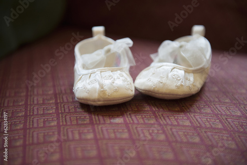 A pair of cream-coloured embroidered satin Christening boots with lace ribbon bows.