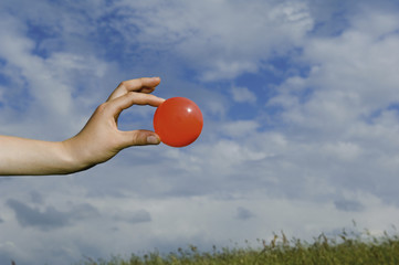 A person's outstretched hand, holding a red ball.