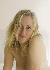 A mature woman with blonde hair and bare skin.