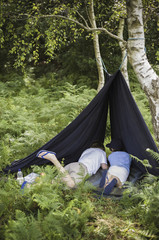 Two boys camping in the New Forest lying under a canvas shelter.