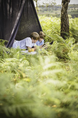Two boys camping in the New Forest, lying under a canvas shelter.