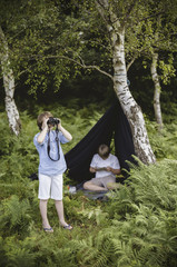 Two boys camping in New Forest. One sitting under a black canvas shelter.  One boy looking through binoculars.