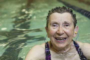 An elderly woman in a swimming pool, taking exercise.