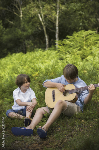 Two boys camping in New Forest. Sitting on the grass, one  playing a guitar.