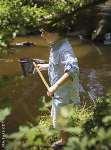A young boy holding a fishing net, by a shallow river. Camping in the New Forest.