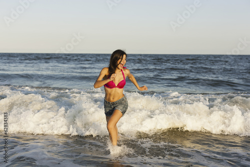 A beautiful young women at the water's edge on the beach in Atlantic City.