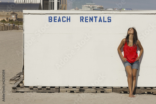 A young woman on the boardwalk at Atlantic City, in New Jersey, by the Beach Rentals stall.
