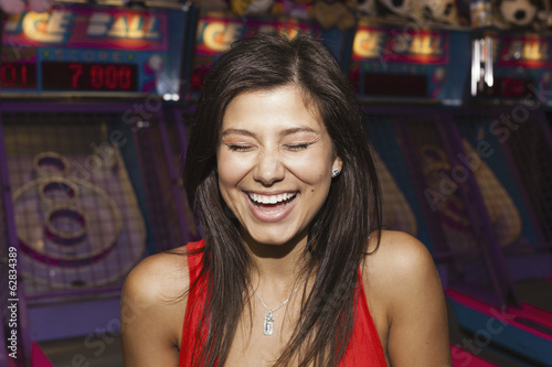 A beautiful young woman on the boardwalk in Atlantic City, in front of a row of slot machines.