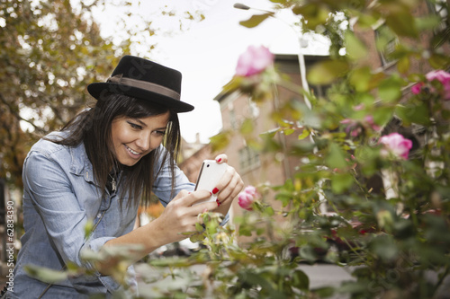 A girl in a brown trilby hat, taking a picture of roses with a smart phone.