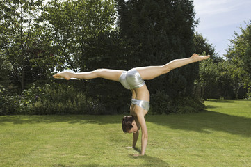 A young woman doing a splits handstand on the grass in a garden.