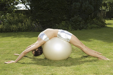 A young woman showing her flexibility, leaning backwards over an exercise ball, with hands and feet on grass.