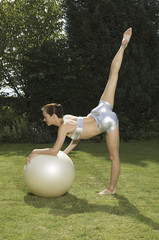 An athlete or gymnast, a young woman leaning on an exercise ball with one leg elevated.