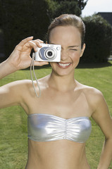 A young woman wearing a silver bandeau top, taking a photograph with a small camera.