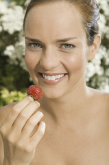 A young woman holding a strawberry.