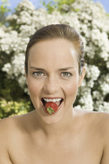 A young woman holding a strawberry between her teeth.