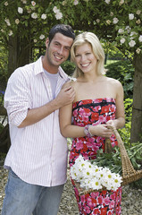 Two people, a  smiling couple, in a garden. A young woman carrying a trug of cut flowers.