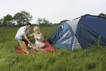A couple, a man and woman seated having a picnic. A blue tent. Camping.