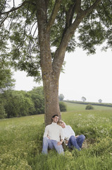 A couple sitting leaning against a tree in a meadow.