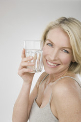 A woman holding a glass of water.